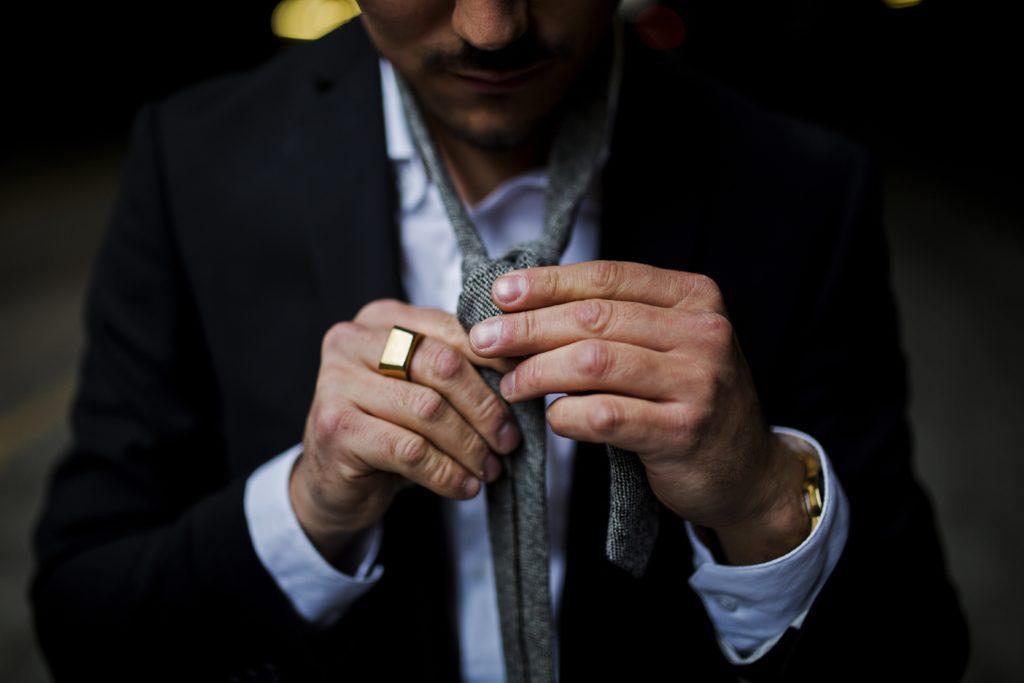 man tying necktie